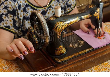 Woman sews on an old sewing machine