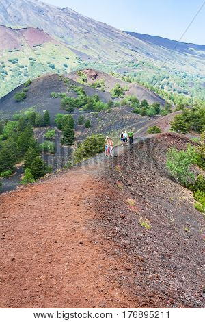 Tourists Walk On Path Between Old Craters