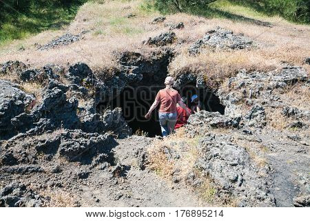 Tourists Visit A Cave In Old Crater Of Volcano