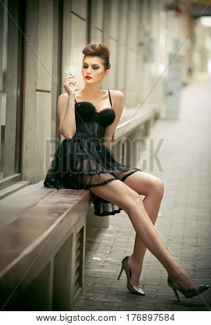 Sensual girl with long legs, short black dress and high heels sitting on the bench. Beautiful young woman wearing short skirt and high heels in urban scenery. Fashion model with long sexy legs on the street