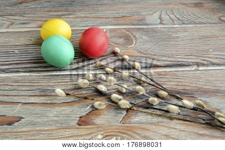 Easter color eggs and willow are a holiday symbol. Eggs and a willow are on a wooden table.