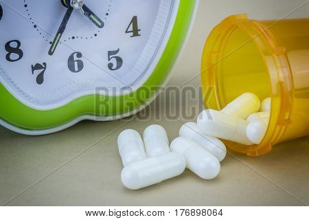 concept for Healthcare And Medicine a clock marks the time of taking medicines