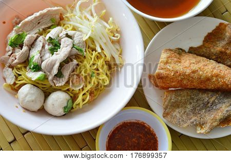 yellow noodle topping pork ball and crispy fish skin with soup