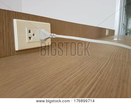 White cable plugged in a white electric outlet mounted on wooden wall background.