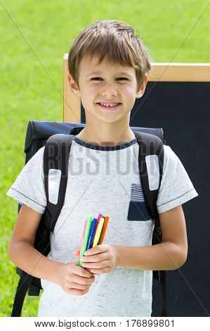 Happy boy with pens and backpack against the blackboard. Education, Back to school concept