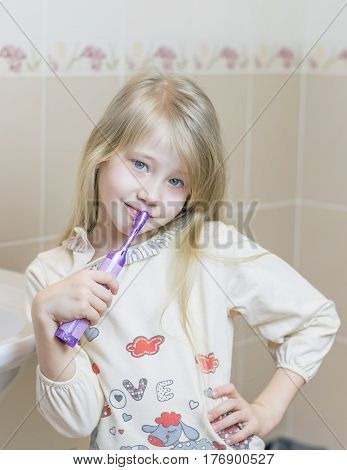 The girl is holding an electric toothbrush in her hand. The concept of oral care.