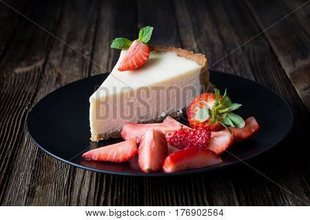 Cheesecake with fresh strawberries on black plate. Slice of plain cheesecake. Wooden table background