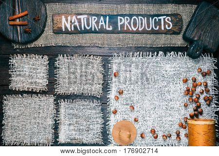 Rustic style template for food and drink industry. Burlap frames on dark wood background with nuts and spices. Wooden cutting boards and signboard with text 'Natural products' as title bar