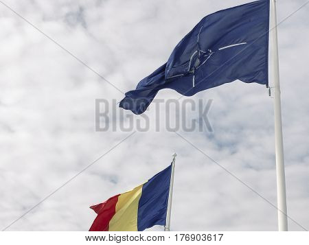 Romanian and Nato flags blowing in the wind