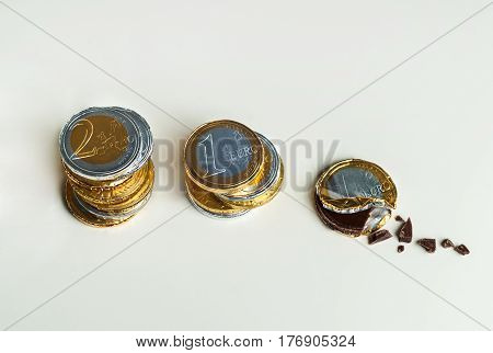 Stacked chocolate euro coins on white background, investment concept