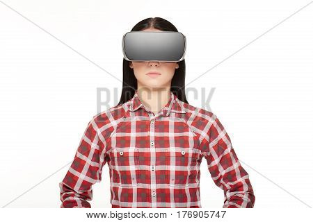 Portrait of young brunette girl in checked shirt wearing in modern headset. Pretty woman in glasses of virtual reality and 3d simulation, new high technology. Studio isolate on white.