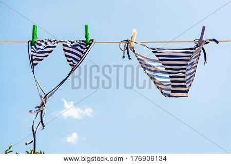 Blue Striped Swimsuit Is Dried On Clothesline