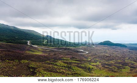 Cloudy Sky Over Road In Lava Fields On Mount Etna
