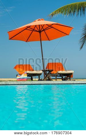 Deckchairs in tropical 5 stars resort hotel swimming  pool