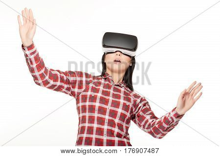 Studio portrait of brunette girl modern in headset of VR surprised looking up with opened mouth.Emotionally woman playing game and watching video in virtual reality glasses and gesturing with rise up.