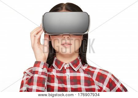 Front view of serious brunette girl wearing in modern headset press buttons and watching video. Pretty woman in checked shirt and glasses of virtual reality and 3d simulation, high technology gadget.