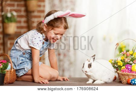 happy easter! happy funny child girl playing with Easter bunny