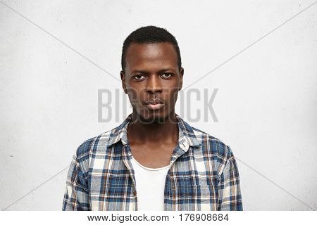 Portrait Of Handsome Young African American Male Dressed In Blue Checkered Shirt Over White T-shirt