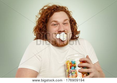 Headshot Of Funny Greedy Fat European Man With Ginger Curly Hair Posing At Studio, Holding Glass Jar