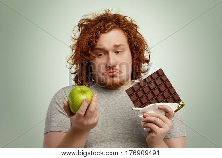 Close Up Portrait Of Doubtful Indecisive Overweight Young Male Facing Dilemma, Can't Decide Between