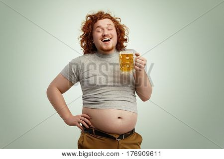 Happy Joyful Young Overweight Man With Curly Red Head Closing Eyes In Enjoyment, Anticipating First