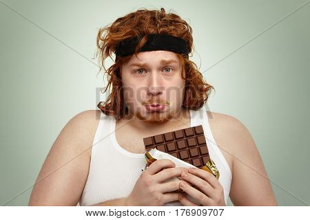Unhappy Obese Redhead Man Wearing Black Sports Headband And White Tank Top Having Sad And Frustrated