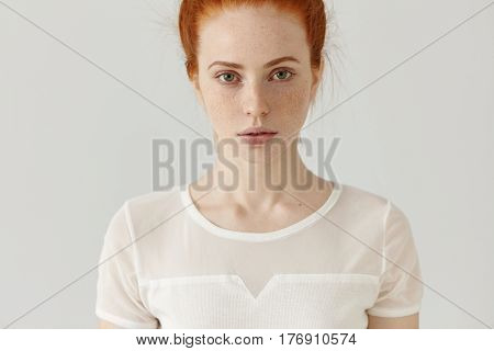 Cropped Studio Shot Of Beautiful Caucasian Female With Red Hair And Freckles Wearing White Top, Stan