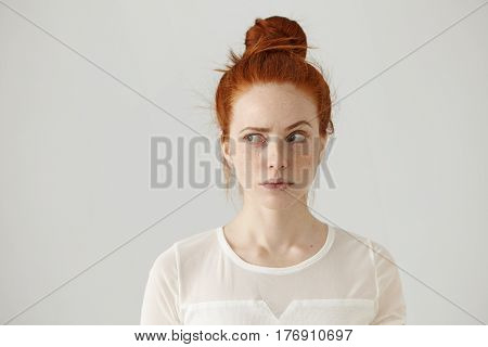 Hmm. Let Me Think. Studio Shot Of Cute Redhead Girl With Hair Knot And Freckles Looking Sideways Wit