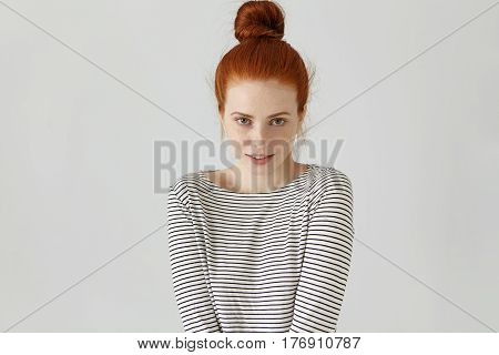 Indoor Shot Of Cute Redhead European Girl With Freckles And Hair Bun Smiling Shyly While Posing In S