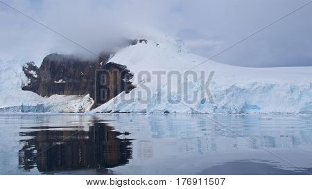 Glacier on Gerlache Strait with reflection on water in Antarctica