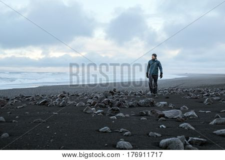 Young man walking on black volcanic beach, Iceland.