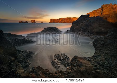 Rocks of Dyrholaey black beach in sunrise light Iceland