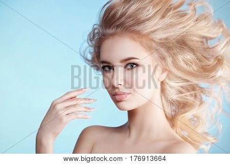 close-up portrait of beautiful curly blondy woman with perfect art make-up, trendy frosted nail design with glitter. Wind in her hair. Studio