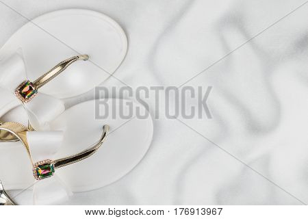 Pair beach white sandals in rhinestones standing on the crumpled white silk. View from above