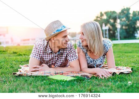 A happy young modern couple in a park on a plaid lies, declaration of love, talking about love, happy family, a teenager's lifestyle, a new family