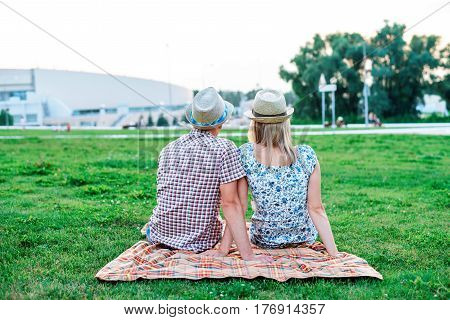 A happy young modern couple a park on plaid lies, declaration of love, talking about love, happy family, teenager's life style, new family, on a rest snack lunch