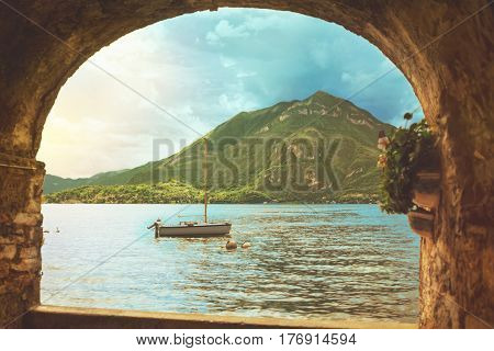 Beautiful colorful panoramic view of waterscape of Como lake coastline with a boat mountain and cloudy sky with a focus on background