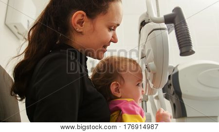 Children ophthalmology - mother and little girl - optometrist Checks Child's Eye, close up