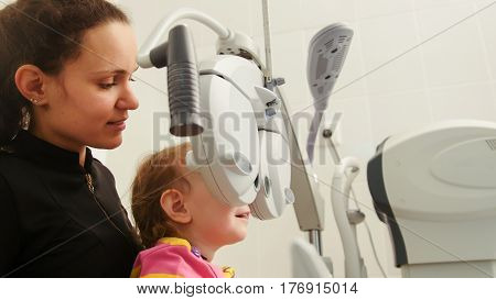 Mother and little girl - optometrist Checks Child's Eye - Children ophthalmology, close up