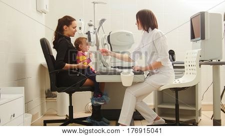 Mother and child in the ophthalmologist's room- optometrist in clinic checking little child's vision, horizontal