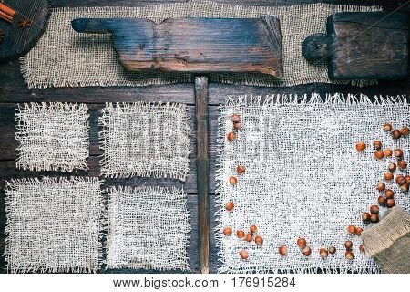 Rustic style template for food and drink industry. Burlap frames on dark wood background with nuts and spices. Wooden cutting boards and pointer with text 'Organic food' as title bar