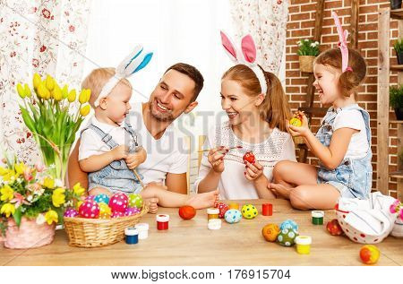 Happy easter! family mother father and children having fun paint and decorate eggs for holiday