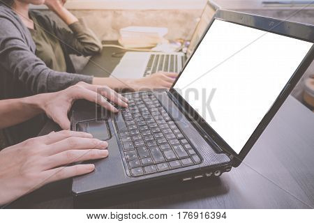 Business partners working together on the same desk they are using a laptop with blank screen Start up business concept
