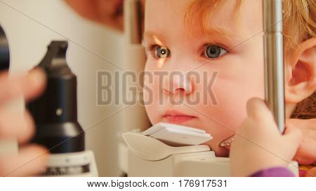 Child's optometry concept - little girl checks eyesight in eye ophthalmological clinic, telephoto