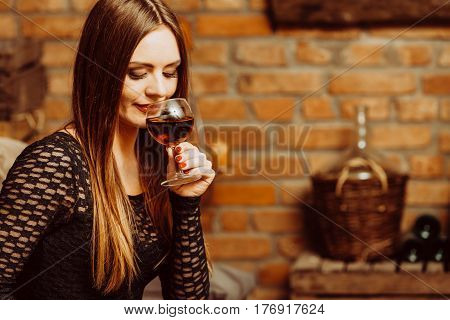 Elegant beauty lady long hair full make up wearing black dress tasting wine in rural cottage interior celler