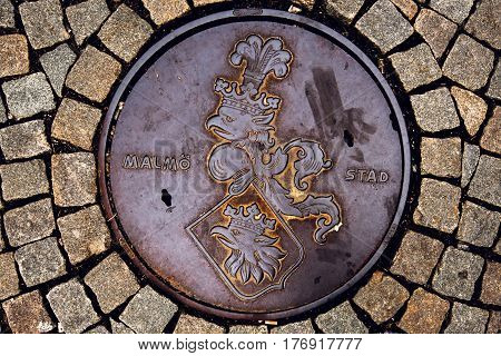 MALMO SWEDEN - MARCH 07 2017: Malmo Stad manhole cover with Coat of arms crowned griffin head is Malmo's municipal arms since 1437th