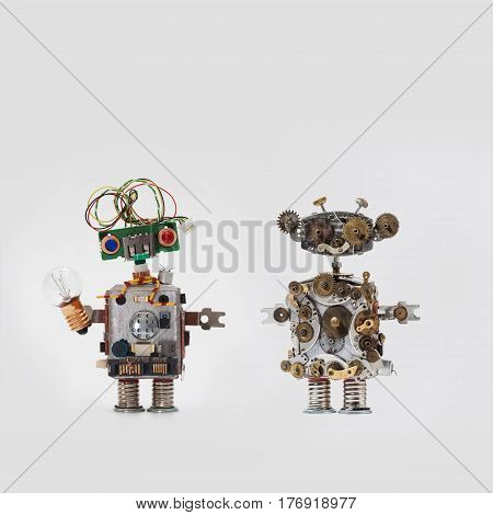 Futuristic robots on gray background. Friendly mechanical toys with electrical wire hairstyle, colored blue red eyes, light bulb. Steampunk style handyman made aged gears, cog wheel hand clock parts.