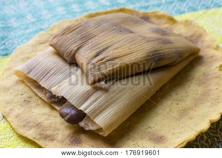 Closeup nutritious Mexican bean tamales wrapped in corn husk on handmade tortilla in Chiapas