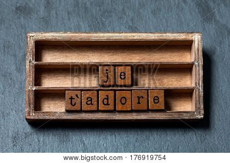 Je t'adore. I love adore you in French translation. Vintage box, wooden cubes phrase written with old style letters. Gray stone textured background. Close-up, up view, soft focus