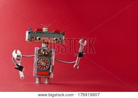 Hand wrench adjustable spanner robot handyman on red background. Friendly service automation toy made of electronic circuits, chip capacitors vintage resistors